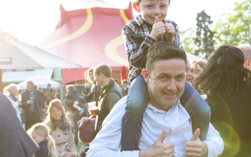 Young boy sitting on the shoulders of a man, both doing the thumbs up sign, at a busy festival with a red and yellow patterned performance tent in the background